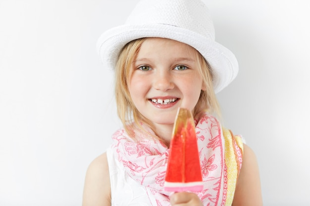 Menina loira de chapéu branco tomando sorvete