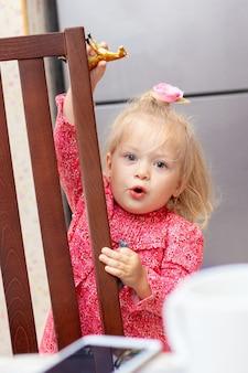 Menina loira de dois anos brincando perto de uma cadeira na cozinha