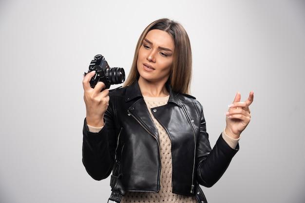 Menina loira de jaqueta de couro preta, verificando sua história fotográfica na dslr e parece insatisfeita.