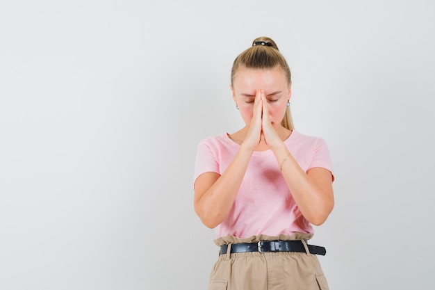 Menina loira de mãos dadas em gesto de oração em t-shirt, calça e olhando calma, vista frontal.