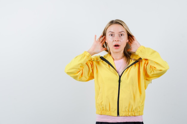 Menina loira de mãos dadas perto da orelha para ouvir algo na camiseta rosa e jaqueta amarela e parecendo surpresa.