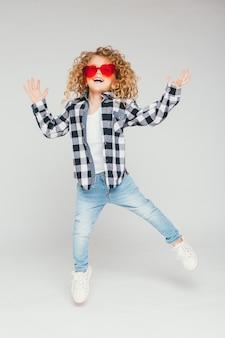 Menina loira de menina em óculos cor de rosa sorrindo