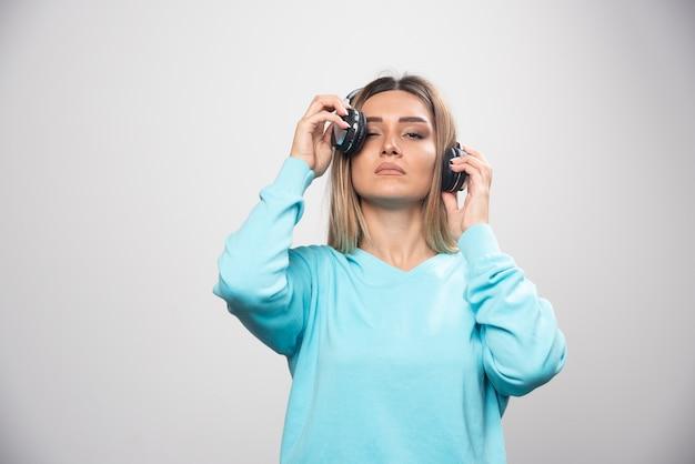 Menina loira de moletom azul posando com fones de ouvido.