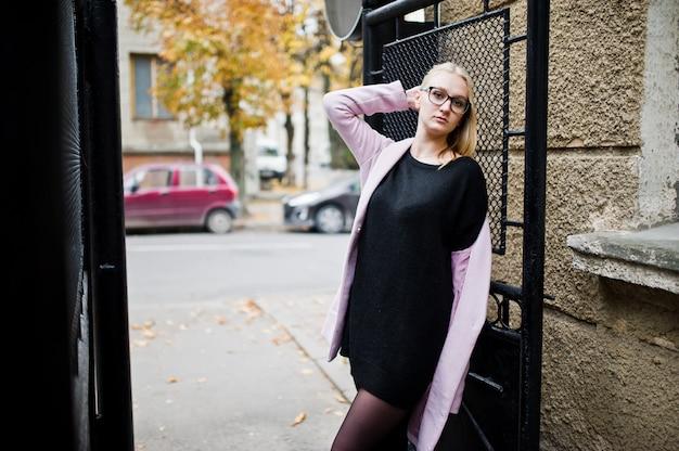 Menina loira de óculos e casaco rosa, túnica preta posada na rua.