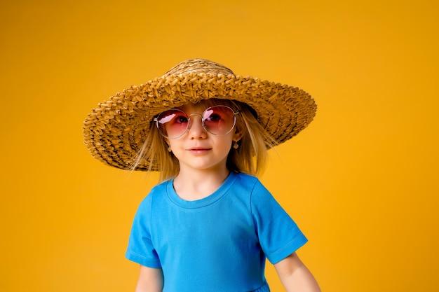Menina loira de óculos escuros e um chapéu de palha em roupas azuis sobre um fundo amarelo de isolar