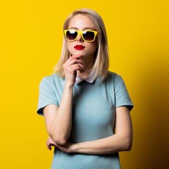 Menina loira de óculos escuros e vestido azul no espaço amarelo