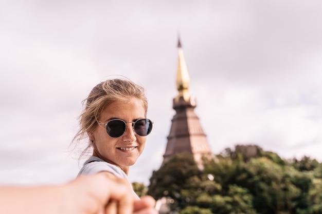 Menina loira de óculos, segurando as mãos na frente de um pagode