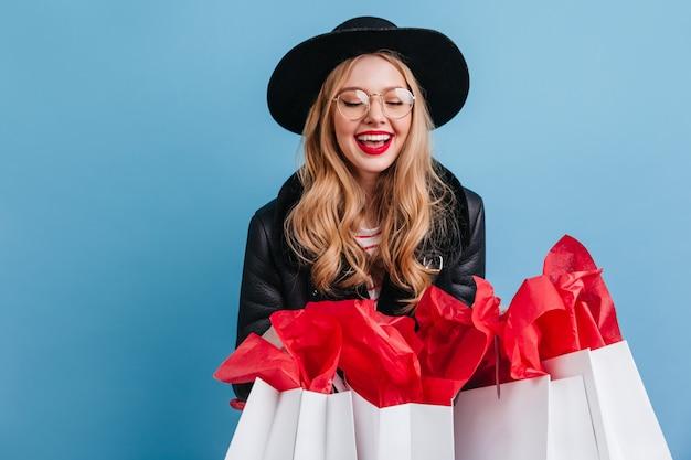 Menina loira de óculos segurando sacolas de compras. shopaholic feminino atraente posando na parede azul.