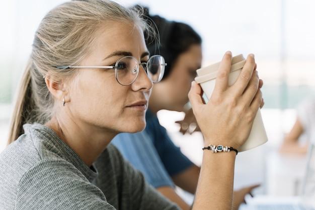 Menina loira de óculos, tomando um café com as duas mãos, sentado em uma mesa
