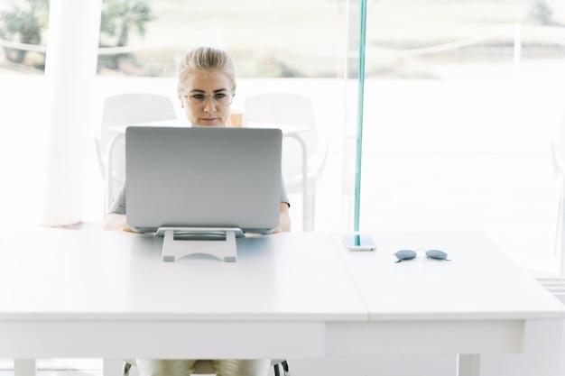 Menina loira de óculos, trabalhando com um laptop