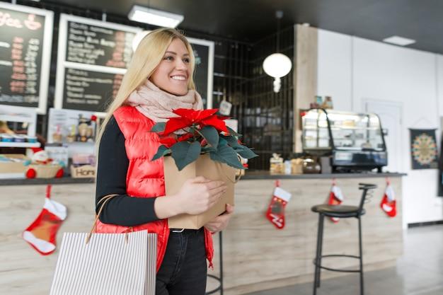 Menina loira de retrato de inverno com compras de natal