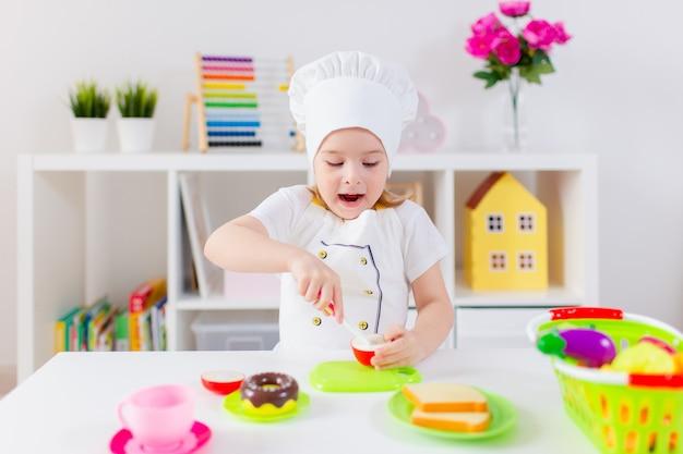 Menina loira de uniforme de cozinheiro branco brincando com frutas e legumes de brinquedo em casa, em jardins de infância ou pré-escola. atividades de jogos para brincar com uma criança em casa