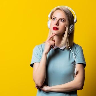 Menina loira de vestido azul com fones de ouvido no espaço amarelo