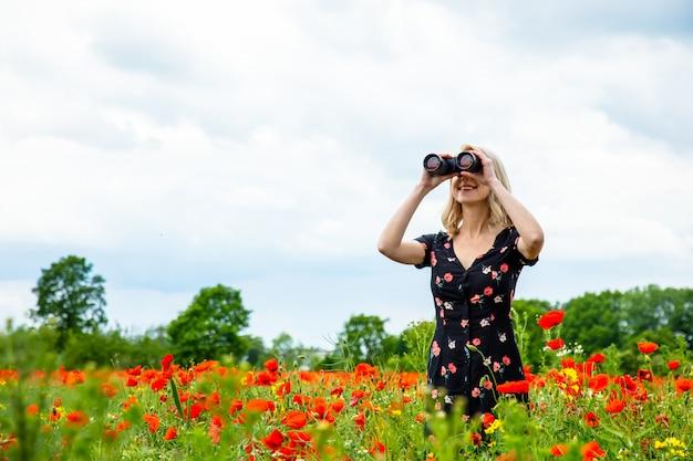 Menina loira de vestido bonito com binóculos no campo de papoulas no horário de verão