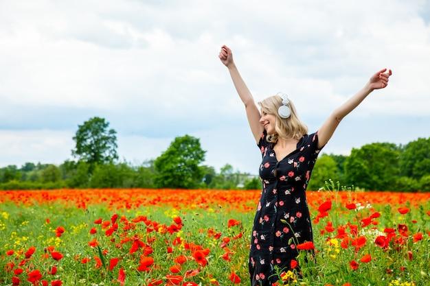Menina loira de vestido bonito com fones de ouvido no campo de papoulas no horário de verão