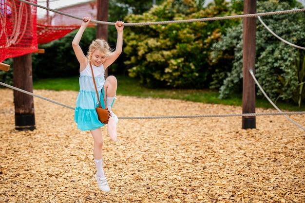 Menina loira de vestido branco e azul, brincando no playground