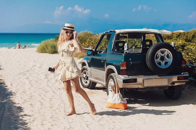 Menina loira de vestido listrado, posando na câmera na praia
