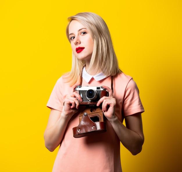 Menina loira de vestido rosa com câmera vintage no espaço amarelo