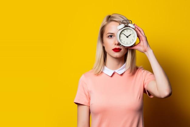 Menina loira de vestido rosa com despertador no espaço amarelo