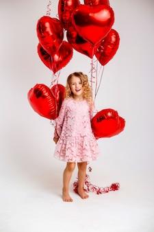 Menina loira de vestido rosa está sorrindo e segurando um monte de balões em forma de coração vermelho conceito de dia dos namorados