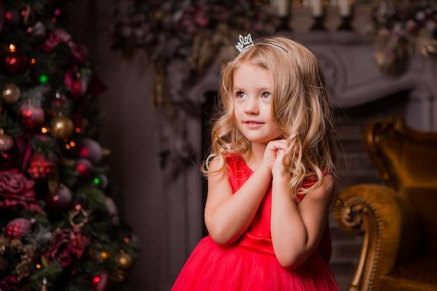 Menina loira de vestido vermelho perto da árvore de natal na sala de estar