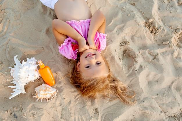 Menina loira, deitado em uma praia de areia sorrindo