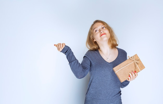 Menina loira demonstrando sua caixa de presente de papelão e se sentindo positiva.