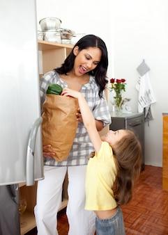 Menina loira descompactar a sacola com sua mãe