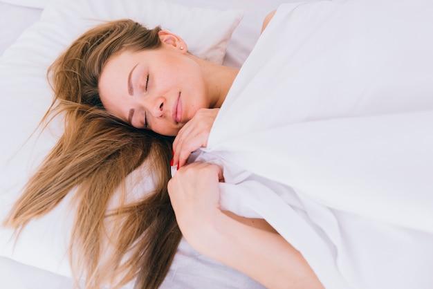 Menina loira dormindo na cama