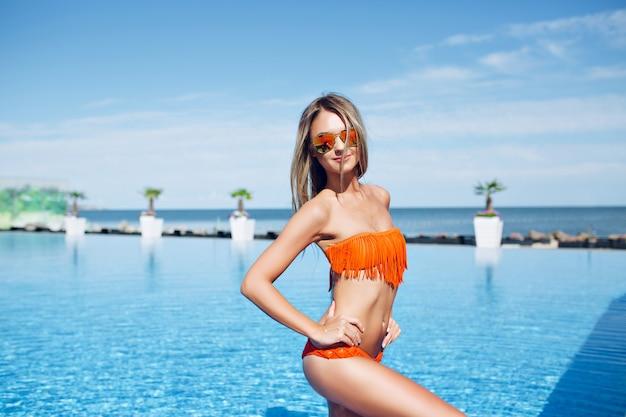 Menina loira e bonita está de pé perto da piscina no sol. ela está posando e sorrindo para a câmera.