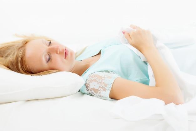 Menina loira e de cabelos compridos dormindo no travesseiro branco
