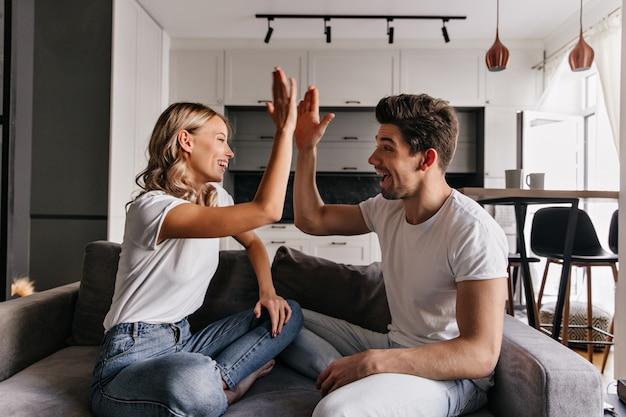 Menina loira elegante brincando com o namorado na sala de estar. retrato interior de jovens a brincar.