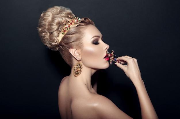Menina loira elegante com cabeleireiro, maquiagem, beijando uma cruz, sobre fundo preto.