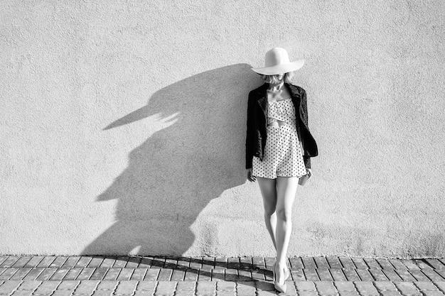 Menina loira elegante e elegante de cabelo curto com chapéu e vestido posando com café sobre branco