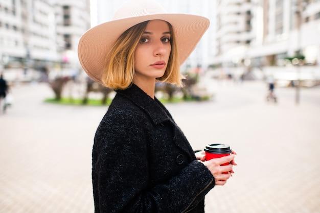 Menina loira elegante elegante de cabelo curto e chapéu posando com café sobre o fundo da rua
