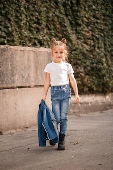 Menina loira elegante em jeans e uma camiseta branca caminha pela rua. menina de 7 anos pequena modelo, linda criança