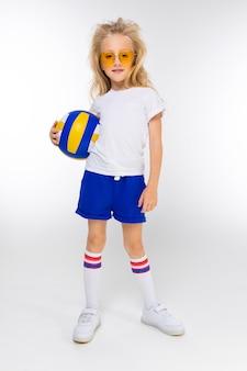 Menina loira elegante em shorts esportivos, uma camiseta e sapatos de ginástica com óculos segura uma bola de basquete em um branco