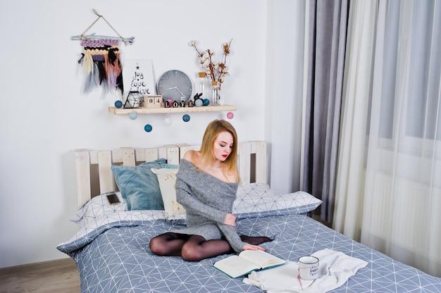 Menina loira elegante usar túnica quente, sentada na cama e ler livro com uma xícara de café quente.
