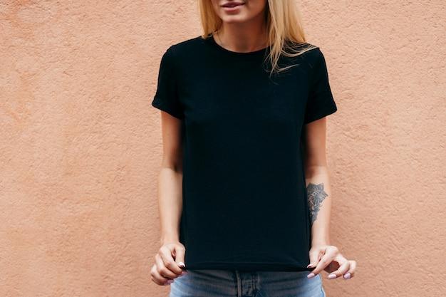 Menina loira elegante vestindo camiseta preta e óculos posando contra a parede