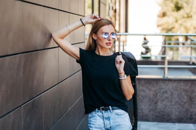 Menina loira elegante vestindo camiseta preta e óculos posando contra a rua