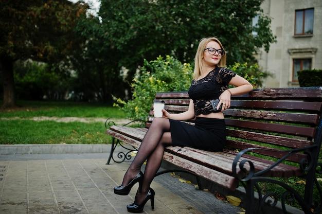 Menina loira elegante vestir preto posando nas ruas da cidade, sentado no banco com uma xícara de café e telefone celular nas mãos.