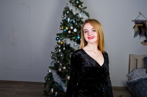 Menina loira elegante vestir vestido preto contra árvore de ano novo com decoração de natal.