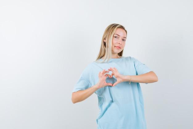 Menina loira em t-shirt azul mostrando um gesto de coração e olhando bonita, vista frontal.
