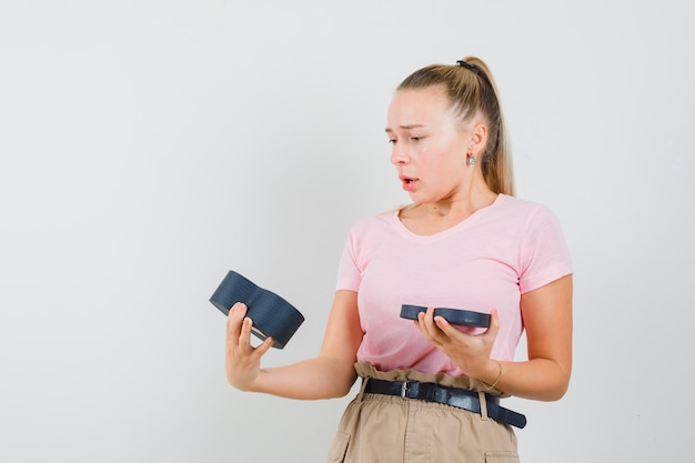 Menina loira em t-shirt, calças olhando para a caixa de presente vazia e parecendo desapontada, vista frontal.