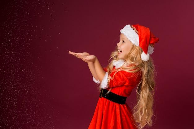 Menina loira em traje de papai noel pega neve