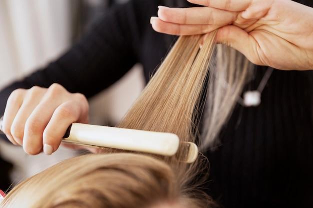 Menina loira em um salão de beleza, fazendo um penteado. fechar-se.