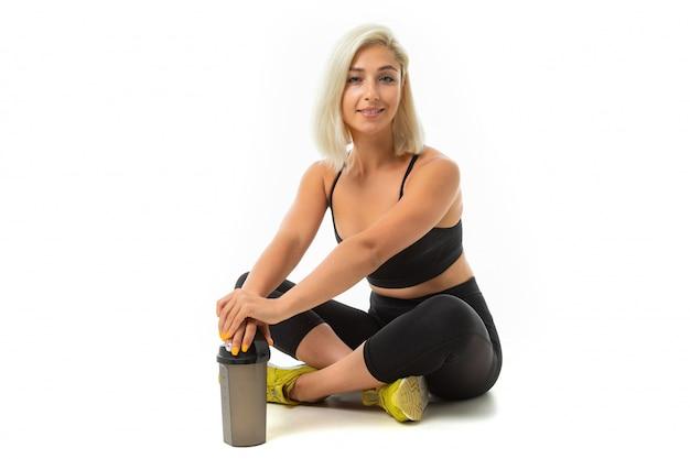 Menina loira em um uniforme preto esportes senta-se no chão com uma garrafa de água