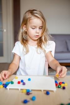 Menina loira em uma camiseta branca, jogando com mosaico multicolorido plástico em casa ou pré-escola. conceito de educação precoce.