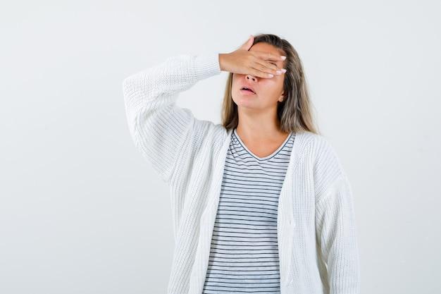 Menina loira em uma camiseta listrada, casaco de lã branco e calças jeans cobrindo os olhos com as mãos e olhando séria, vista frontal.