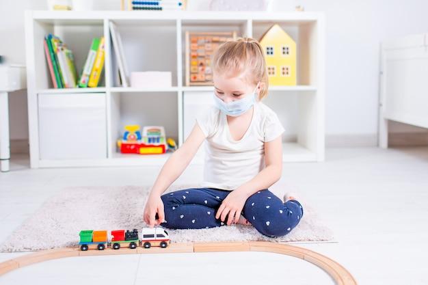 Menina loira em uma máscara médica brincando com trem de brinquedo no chão em uma sala de luz em casa durante a quarentena.